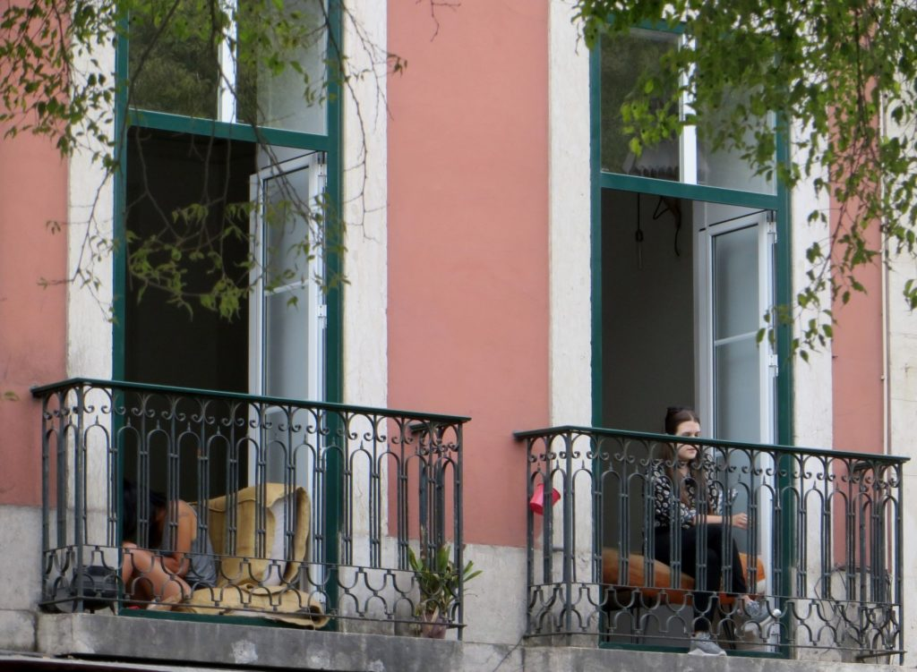 Jung ladies on balconies in Lisbon