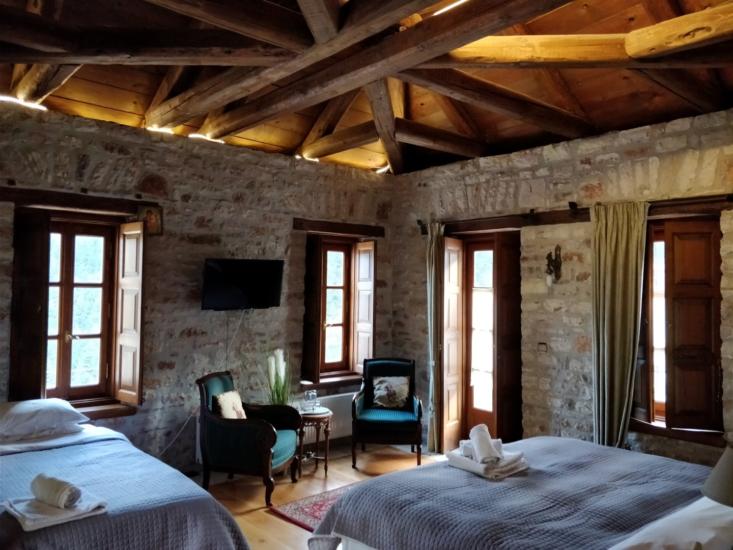 hotel room with two beds and stone walls and wooden roof
