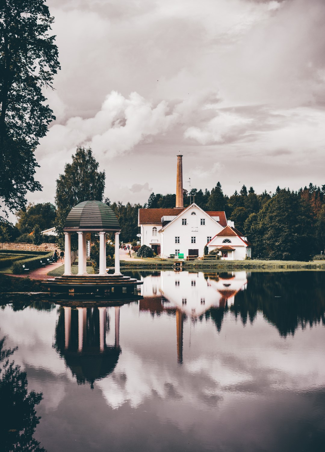 white house with a chimney on a lake on a cloudy day